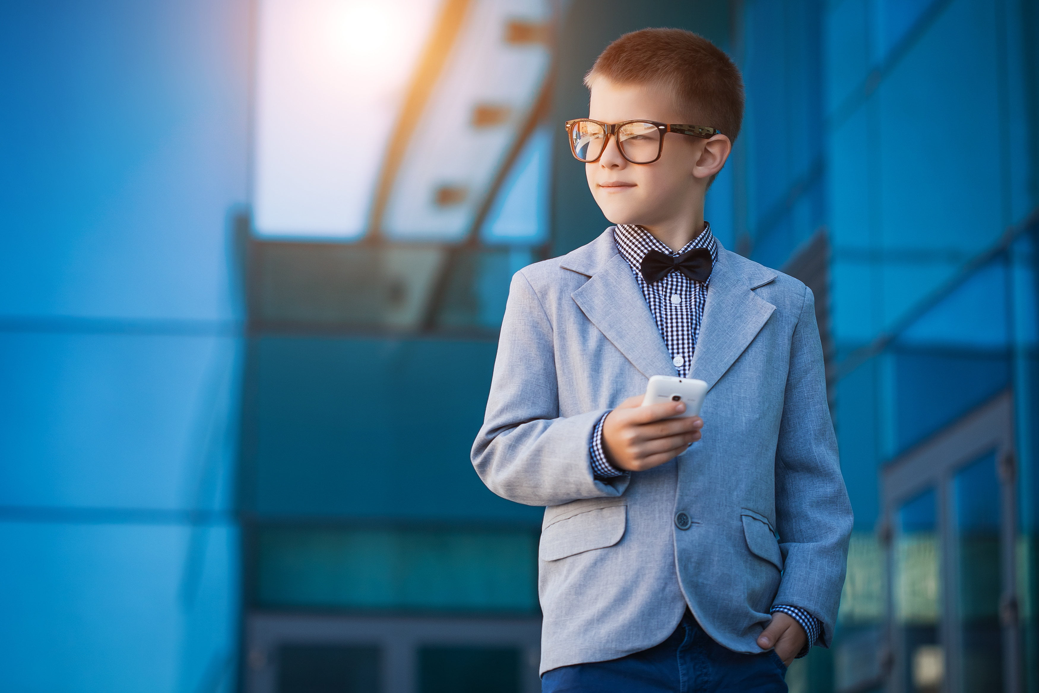 Portrait of a kid businessman next to tall buildings